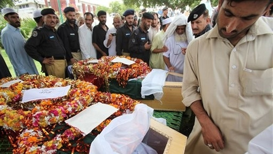 Aug. 11: Pakistani police officers and others look at their colleagues and friends who lost their lives in a suicide bombing in Peshawar, Pakistan. A female suicide bomber detonated her explosives near police guarding the scene of an explosion earlier Thursday in this northwestern Pakistani city, a rare double-pronged attack that killed many people.
