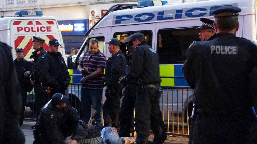 Aug. 10: Police officers hold a local man who was inebriated outside a pub on Eltham High Street in London.  A large group of local men gathered in the area on Wednesday to deter looters and a large number of police officers was also present to prevent any vigilante actions.