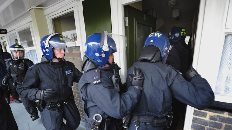 Aug. 11: Metropolitan Police officers prepare to carry out a raid on a property on the Churchill Gardens estate in Pimlico, London during an operation where police hope to recover property stolen during the recent disturbances in the capital.
