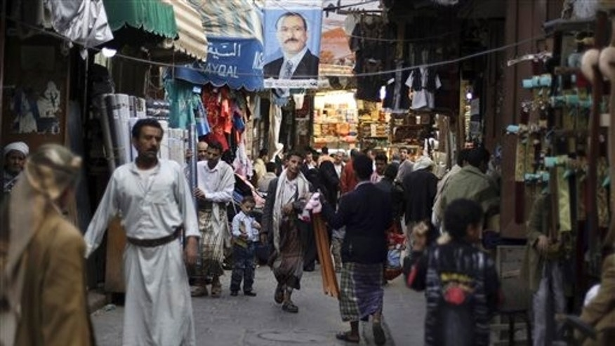 Aug. 9: People walk past vendors selling goods, beneath a poster showing Yemen's President Ali Abdullah Saleh, in a street leading to the old city of Sanaa, Yemen. The U.S. and Saudi Arabia pressured Yemen's president Ali Abdullah Saleh to stay in Saudi Arabia after he was released from a lengthy hospital stay to treat wounds suffered in an assassination attempt, according to Yemeni officials.