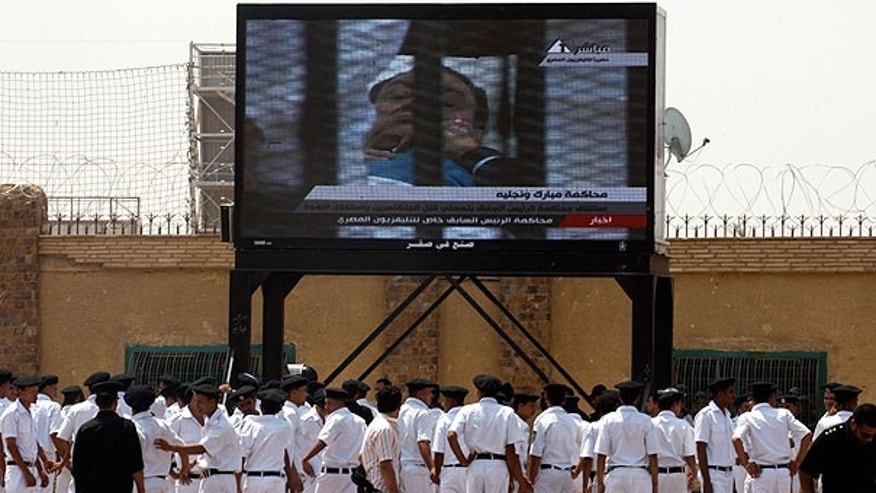 Aug. 15: Egyptian police officers watch 83-year-old former Egyptian president Hosni Mubarak on a bed in the defendants' cage from the courtroom live on a large TV screen outside the Police Military Academy complex in Cairo, Egypt.