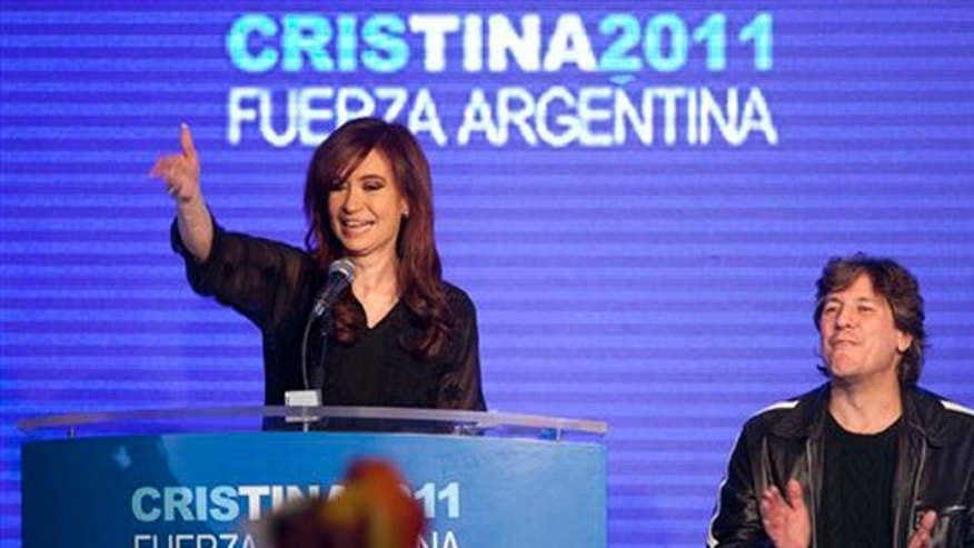 Argentina's President and candidate for re-election Cristina Fernandez, left, and Amado Boudou, Argentina's Minister of Economy and vice-presidential candidate, celebrate with supporters after the primary elections in Buenos Aires, Argentina, Sunday Aug. 14, 2011.
