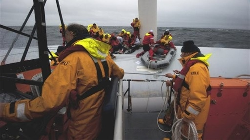 Aug. 15: This image made available by the Royal National Lifeboat Institute shows the Baltimore, Ireland, RNLI lifeboat crew taking part in a major rescue operation Monday evening, as a member of the yacht's crew is placed in a dingy on the yacht's upturned hull for transfer to the lifeboat. British sea rescue workers say that 21 people were rescued after their U.S.-registered racing yacht capsized off the Irish coast.