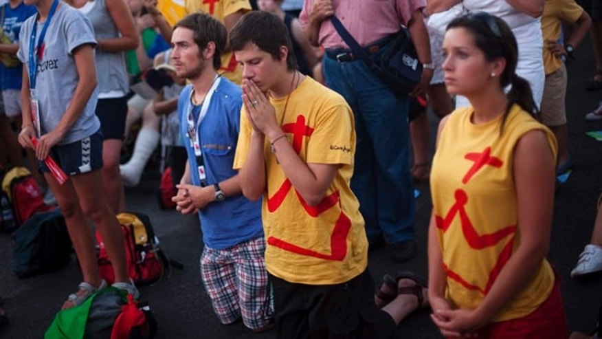 Pilgrims pray at the street during a mass at the Cibeles square, Tuesday Aug. 16, 2011, ahead to the visit of Pope Benedict XVI in Madrid next Aug. 18- 21. (AP Photo/Emilio Morenatti)