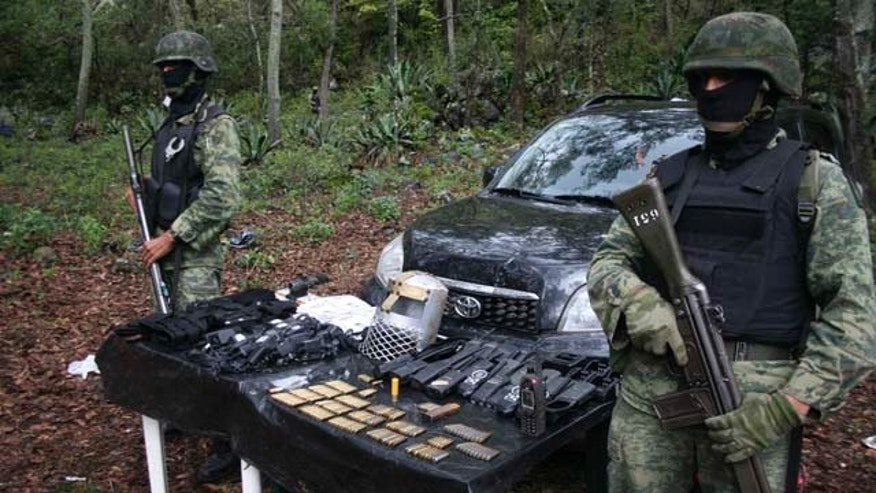 Soldiers stand next to munitions, communications gear and a medieval style bascinet that were seized when a training camp was discovered after a firefight between Mexican army soldiers and gunmen in the woods near the town of Santa Gertrudis, Mexico. The Templar Knights, a new drug cartel that was created after it splintered from the La Familia cartel last March, has issued a code-of-conduct booklet for members saying it is fighting a war against tyranny and injustice. (AP Photo)