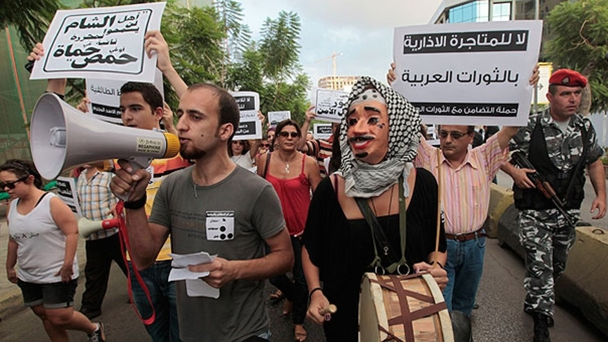 Aug. 15: Lebanese anti-Syrian regime protesters shout slogans against Syrian President Bashar Assad as they hold up Arabic placards as they protest during a demonstration in Beirut, Lebanon.