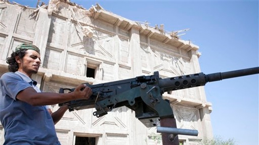 Aug. 17: In this photo, a Libyan rebel fighter readies his weapon before heading to the front line in Sabratha, 50 miles west of Tripoli, Libya.