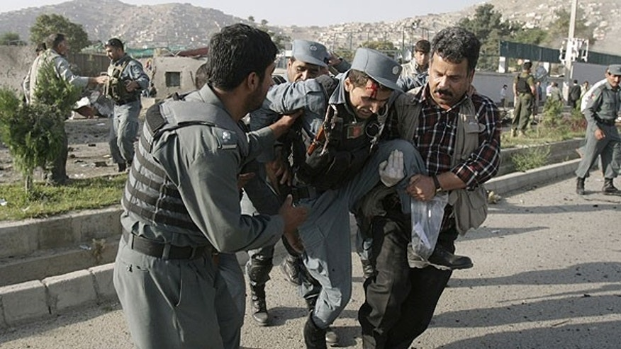 August 19: Afghan security forces carry a wounded police man at the site of a suicide attack outside The British Council in Kabul, Afghanistan.