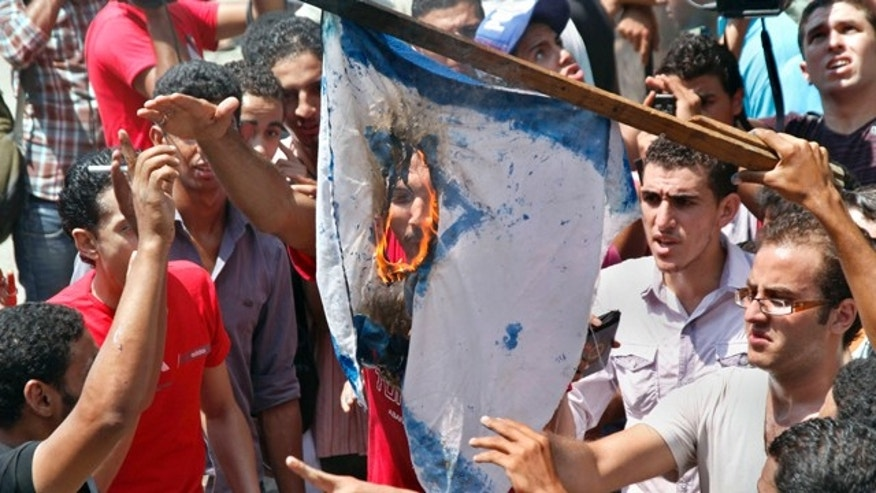 Aug. 20: Egyptian protesters burn an Israeli flag during anti-Israel protest in front of Israeli embassy in Cairo, Egypt, to protest the deaths of Egyptian security forces killed in a shootout between Israeli soldiers and Palestinian militants on Thursday in the Sinai.