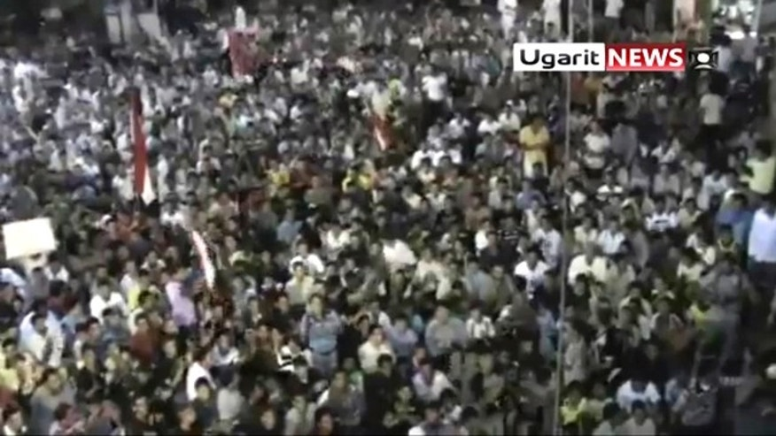 """Aug. 18: In this image from amateur video by the Ugarit News group, a large crowd reportedly gathered in the town of Rastan near Homs on Wed., Aug 17, during which people chanted """"Rastan demands the execution of the president."""""""