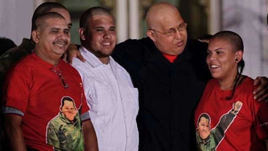 Aug. 21, 2011: Venezuela's President Hugo Chávez,second from right, poses for pictures with people from Dominican Republic who shaved their heads in solidarity with  his struggle against cancer at Miraflores presidential palace in Caracas, Venezuela.