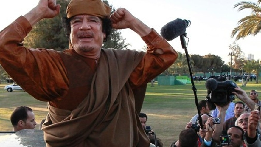 FILE - In this April 10, 2011 file photo, Libyan leader Moammar Gadhafi gestures to his supporters in Tripoli, Libya. As rebels swarmed into Tripoli late Sunday, Aug. 21, 2011, and Gadhafi's son and one-time heir apparent Seif al-Islam was arrested, Gadhafi's rule was all but over, even though some loyalists continued to resist. (AP Photo/Pier Paolo Cito, File)
