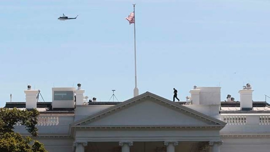 US Park Service helicopter patrols over the White House in Washington, Tuesday, Aug. 23, 2011, as a member of the Secret Service walks across the roof of the White House following an earthquake in the Washington area. The 5.9 magnitude earthquake centered northwest of Richmond, Va., shook much of Washington, D.C., and was felt as far north as Rhode Island and New York City.  (AP Photo/Pablo Martinez Monsivais)