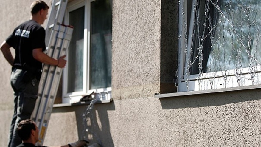 In this photo taken Aug. 22, police remove barbed wire from an apartment window in Hamburg. Germany. Officers were still on the scene on Aug. 24, five days after an alleged victim escaped the apartment.