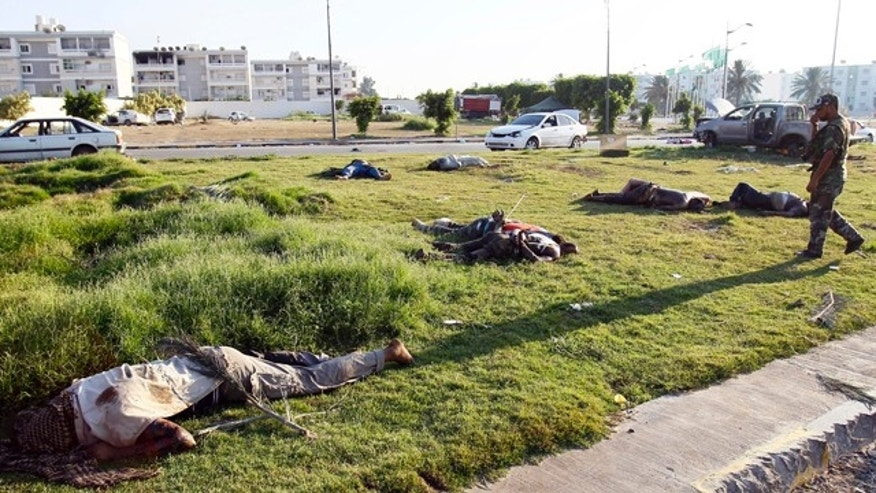 Aug. 25: Libyan rebel walks by dead bodies in Abu Salim district in Tripoli, Libya.