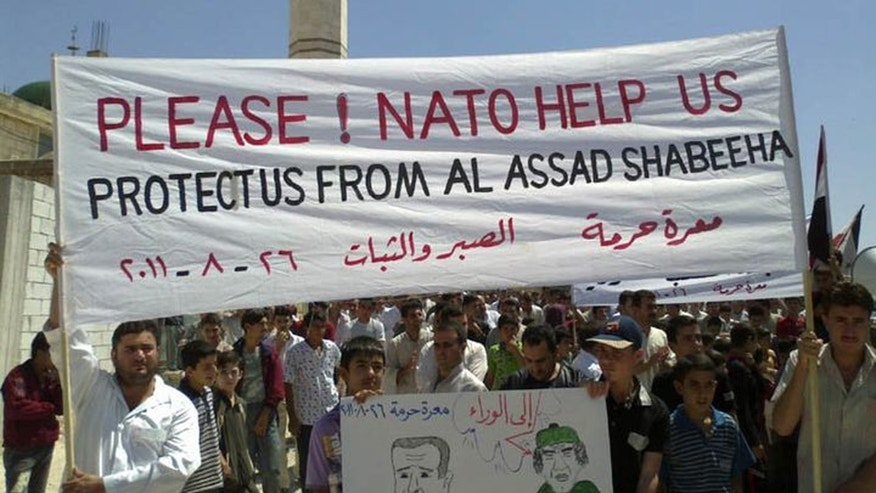 Anti-Syrian President Bashar Assad protesters, hold up a banner pleading for help from Nato, during a demonstration against the Syrian regime, at Maaret Harma village, in Edlib province, Syria, on Friday Aug. 26, 2011.