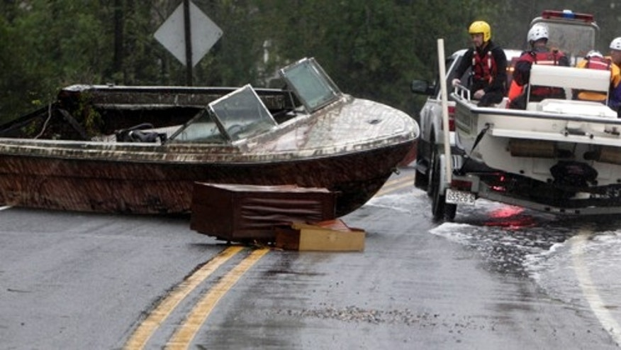The Arr-Mac water rescue team from Wayne County maneuvers around a beached boat in the middle of Hwy. 304 Saturday, Aug. 27, 2011 in Mesic, N.C. Hurricane Irene knocked out power and piers in North Carolina, clobbered Virginia with wind and churned up the coast Saturday to confront cities more accustomed to snowstorms than tropical storms. New York City emptied its streets and subways and waited with an eerie quiet. (AP Photo/The News & Observer, Chris Seward)