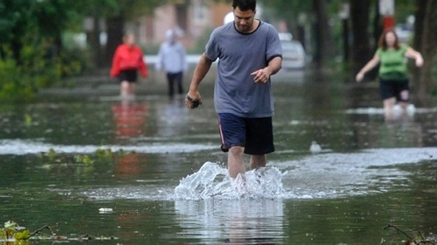 Aug 28: Tony Pena wades through a flooded Lorraine Road in Island Park, N.Y. after Tropical Storm Irene, downgraded from a hurricane, swept through Long Island.(AP Photo/Kathy Kmonicek)