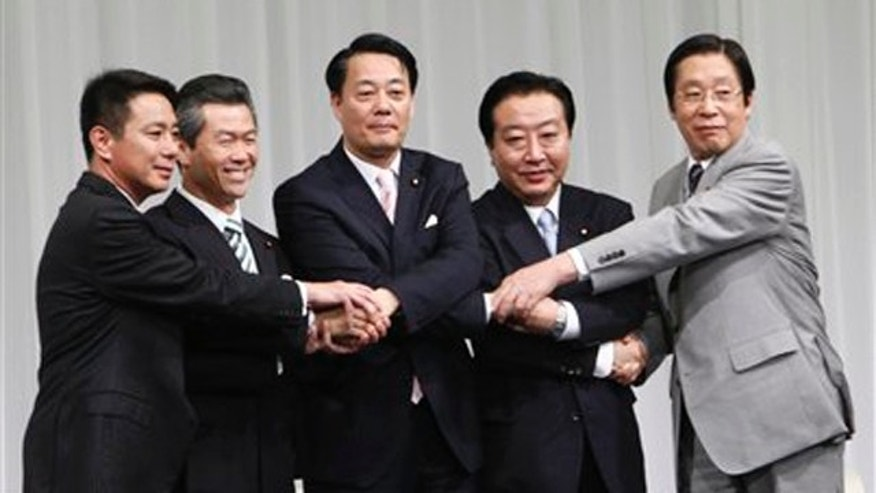 Candidates for the leader of Japan's ruling Democratic Party, from left, former Foreign Minister Seiji Maehara, former Transport Minister Sumio Mabuchi, Trade and Economy Minister Banri Kaieda, Finance Minister Yoshihiko Noda and Farm Minister Michihiko Kano, join their hands prior to a debate in Tokyo Sunday, Aug. 28, 2011.