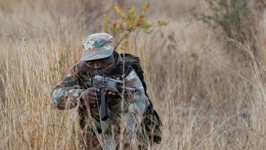 July 20: A member of the South African National Defence Force poses for photographers during a media visit to clandestine positions at the Kruger National Park. South Africa's military has deployed troops in the park near its border with Mozambique to cut down on rhino poaching, which kills several hundred of the animals a year.