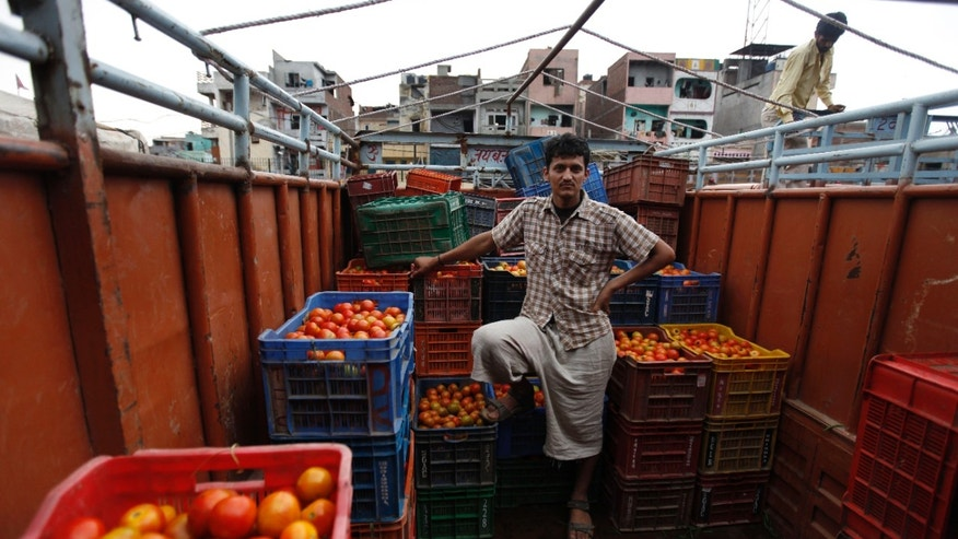 August 3: Indian tomato farmer Sunil Sharma stands in a truck with produce from his tomato farm, as it is unloaded, at one of Asia's biggest wholesale markets, Azadpur mandi, in New Delhi, India.