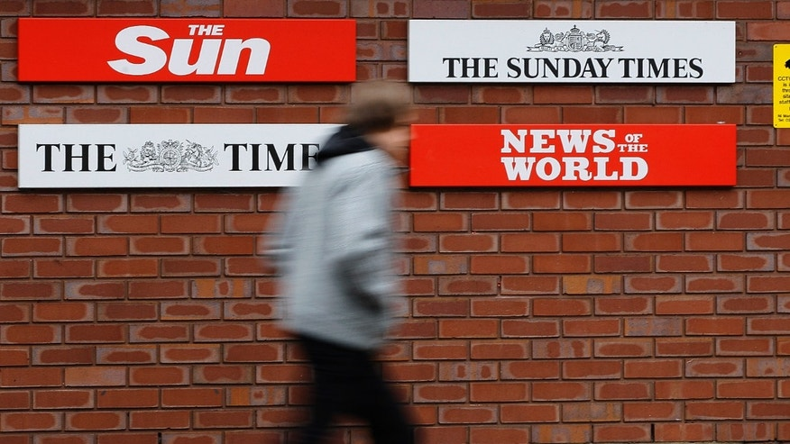 January 27: A pedestrian passes signs at the entrance to News International in Wapping, London. A person familiar with the matter says that a review launched at Rupert Murdoch's News International in the wake of the tabloid phone hacking scandal will also weigh journalistic standards at its other British titles, including The Times of London.