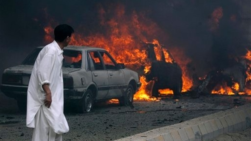 August 31: A Pakistani looks to burning cars after a suicide bombing in Quetta, Pakistan.