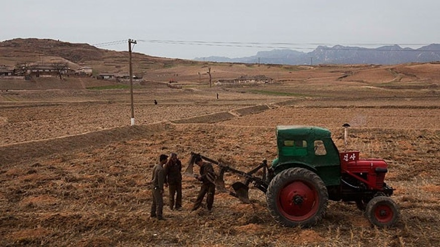 In this Tuesday, April 17, 2011 file photo, men check a plow and tractor in a field along the highway near the southern city of Kaesong, south of Pyongyang, North Korea.
