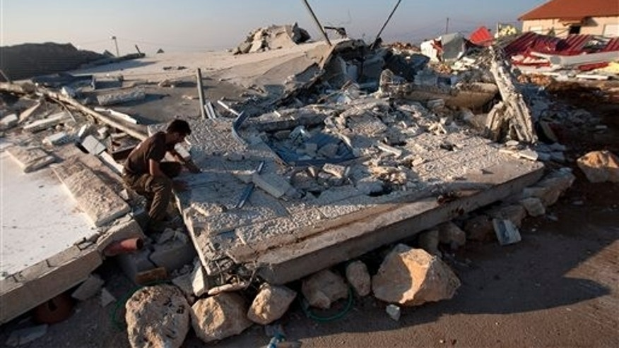 Sept. 5, 2011: A Jewish settler sits on the rubble of a house demolished by the Israeli authorities in the West Bank settlement of Migron near the Palestinian city of Ramallah.