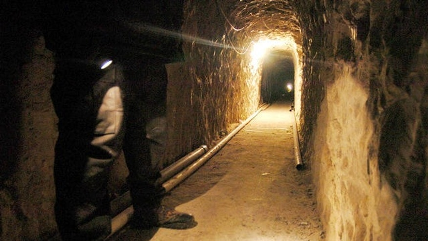 A Mexican federal policeman shines his flash light on the ground of a sophisticated clandestine tunnel that passes under the US-Mexico border on Wednesday, January 25, 2006 in Tijuana, Mexico. In August, 2011, Mexican police found another tunnel believed to have been used to smuggle people into the United States.
