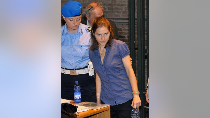 Knox is escorted by a police officer as she arrives for an hearing of her appeals case at the Perugia court, Italy, Sept. 5.