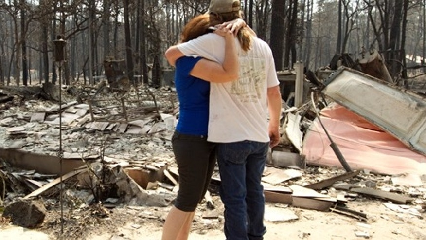 Nathan and Deborah Torkelson embrace on Tuesday Sept. 6, 2011, outside their home that was destroyed by fire near Bastrop, Texas.  More than 1,000 homes have been destroyed in at least 57 wildfires across rain-starved Texas, most of them in one devastating blaze near Austin that is still raging out of control, officials said Tuesday.  (AP Photo/Austin American-Statesman,  Jay Janner  MAGS OUT; NO SALES; TV OUT; INTERNET OUT; AP MEMBERS ONLY