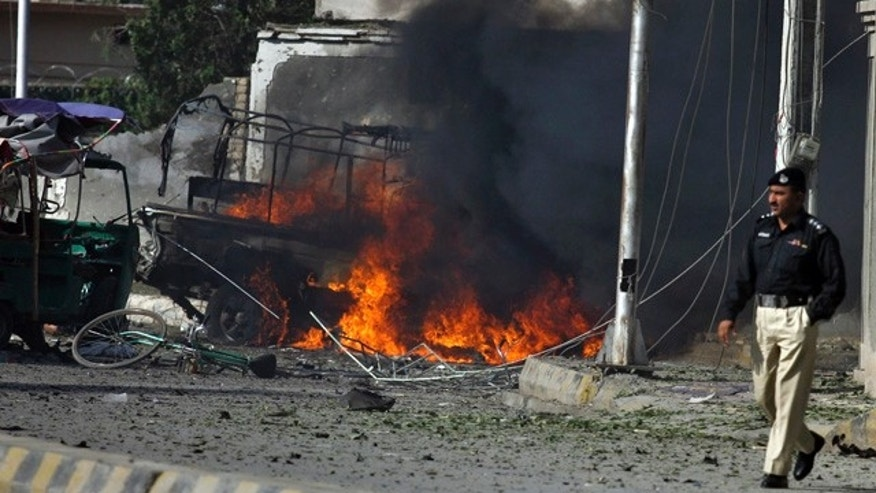 Sept. 7: Pakistani police officer walks past burning vehicle at the site of suicide bombing in Quetta, Pakistan.