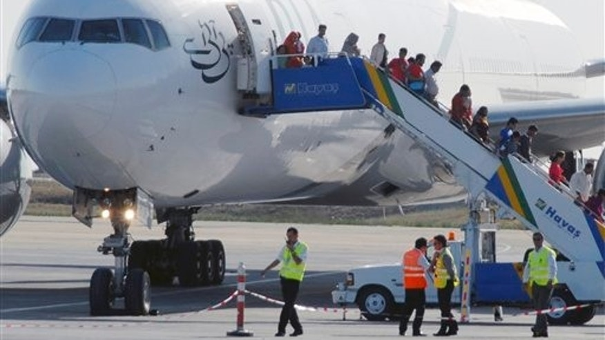 Septembr 7: Passengers disembark from a Pakistan International Airlines plane on a flight between Islamabad and  Manchester, England, that was forced to make an emergency landing because of a bomb threat over Bulgaria, sits on the tarmac at Ataturk Airport in Istanbul, Turkey