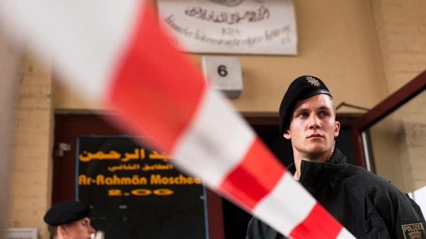Sept. 8: A German police officers stand guard outside an Islamic cultural center as others conduct a search, in Berlin.