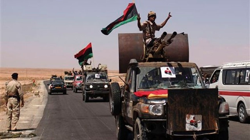 September 8: Libyan fighters head to the frontline through the last checkpoint before Bani Walid, in Wai Dinar, Libya.