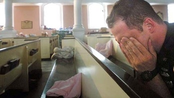 NEW YORK - SEPTEMBER 21, 2001:  (SEPTEMBER 11 RETROSPECTIVE) NYPD police officer Ken Radigan rubs his eyes after briefly sleeping in a pew at St. Paul's Episcopal Chapel, near the site of the World Trade Center attack, September 21, 2001 in New York City.  The chapel is serving as a relief area for rescue workers. (Photo by Mario Tama/Getty Images)