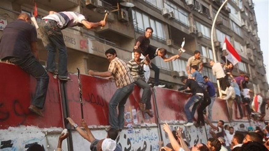 Sept. 9: Some hundreds of Egyptian activists demolish a concrete wall built around a building housing the Israeli embassy in Cairo, Egypt, to protect it against demonstrators, as they raise their national flag.