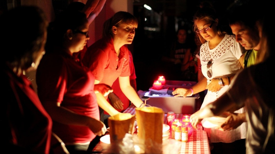 SAN DIEGO, CA - SEPTEMBER 8:  Workers serve pizza to customers outside of Filippi's Pizza after a massive blackout hit Southern California September 8, 2011 in San Diego, California. Approximateely 1.5 million residents from Southern Orange County to Northern Baja are without power.(Photo by Sandy Huffaker/Getty Images)