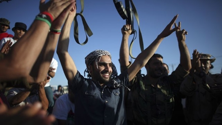 September 10: Former rebel fighters celebrate prior to heading to the frontline in Bani Walid, at a checkpoint between Tarhouna and Bani Walid.