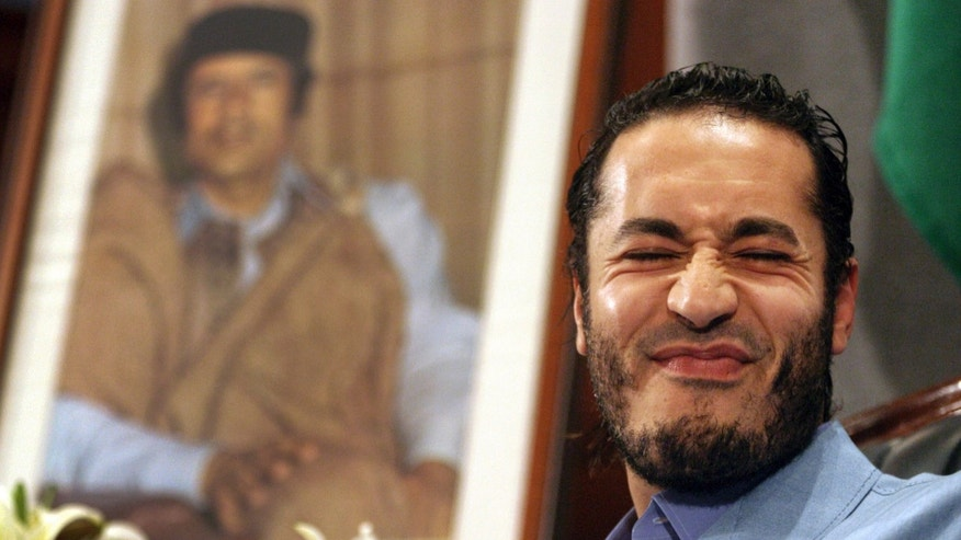 In this file photo of  Monday, Feb. 7, 2005 Al-Saadi Gadhafi, the son of Libyan leader Moammar Gadhafi, reacts in front of the leader's portrait during a press conference in Sydney, Australia. The spokesman for Niger's government announced Sunday that Libyan leader Muammar Qaddafi's son Al-Saadi has entered the country via the northern desert separating the landlocked African nation from Libya.