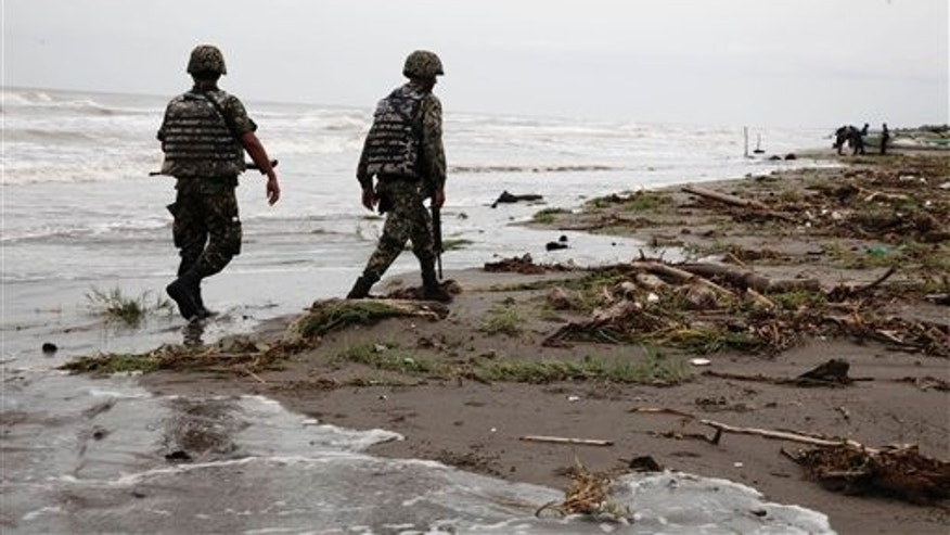 Sept. 10: Navy officers walk along El Bosque beach, in Mexico's Tabasco state. Mexico's state oil company and a Texas-based company searched for 10 missing oil workers on Friday, including four Americans, who evacuated from a research vessel in the Gulf of Mexico ahead of Tropical Storm Nate.