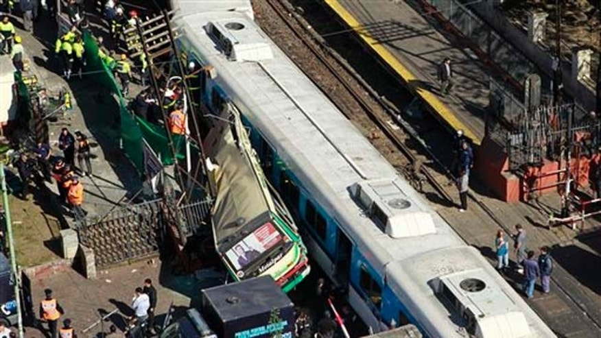 View of a crash between two passenger trains and a bus in Buenos Aires, Argentina, Tuesday, Sept. 13, 2011. At least seven people were killed and over 162 injured in a rush-hour crash involving two trains and a bus whose driver drove around barriers in an attempt to beat them across the tracks, Argentine authorities said. (AP Photo/Victor R. Caivano)