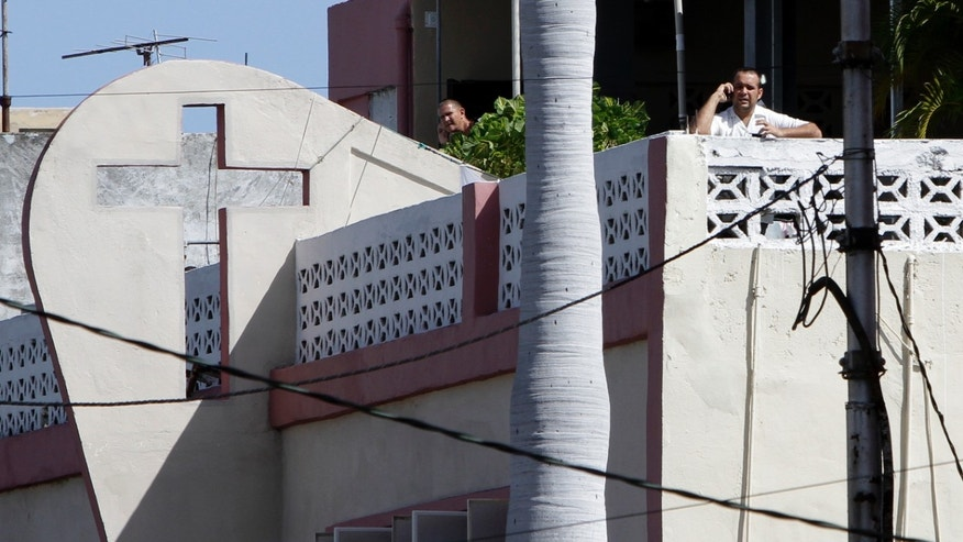 Sept. 13: William Herrera, son of the Church's pastor Braulio Herrera, right, speaks on a cellphone during an interview with The Associated Press on the roof of the Assembly of God Pentecostal Church in Havana, Cuba. Herrera and 60 believers remain in spiritual retreat since last Aug. 21.