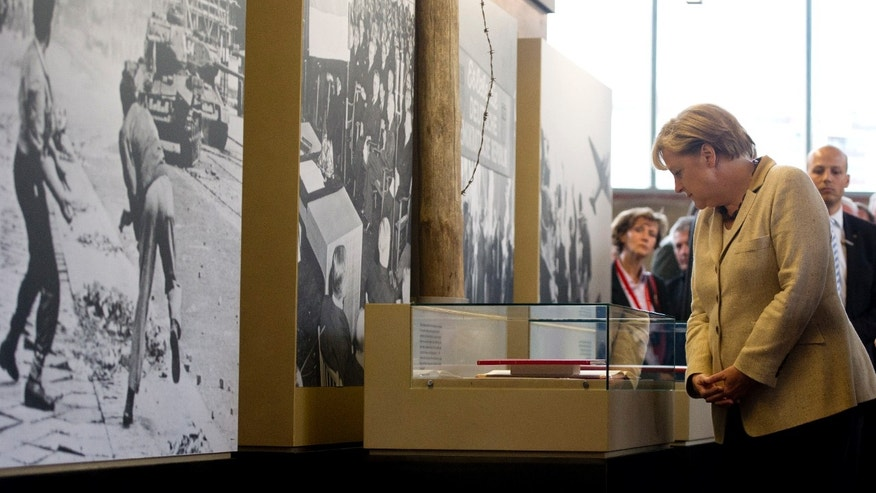 "German Chancellor Angela Merkel views exhibits at a permanent exhibition on Germany's Cold War past at what was once one of East Berlin's busiest border crossings, in Berlin, Germany, Wednesday, Sept. 14, 2011. The exhibition is housed in the restored 1960's building where passport and customs checks were carried out at Berlin's Friedrichstrasse station. It was popularly known as the ""Traenenpalast,"" or ""Palace of Tears."""