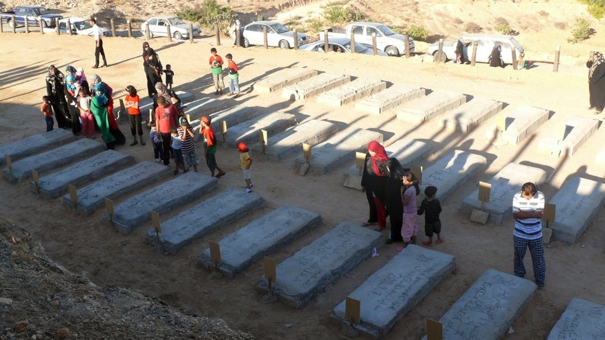 Sept 7, 2011: Libya women pay respect on the tombs of relatives reburied after been unearthed from a mass grave of 35 men in Galaa, Nafusa mountains, 120 kms from Tripoli, Libya, Friday, Sept. 9, 2011. Residents of Galaa unearthed a mass grave of 35 men, in some cases relatives digging up the remains of loved ones who had allegedly been blindfolded, bound and shot by Gadhafi guards.