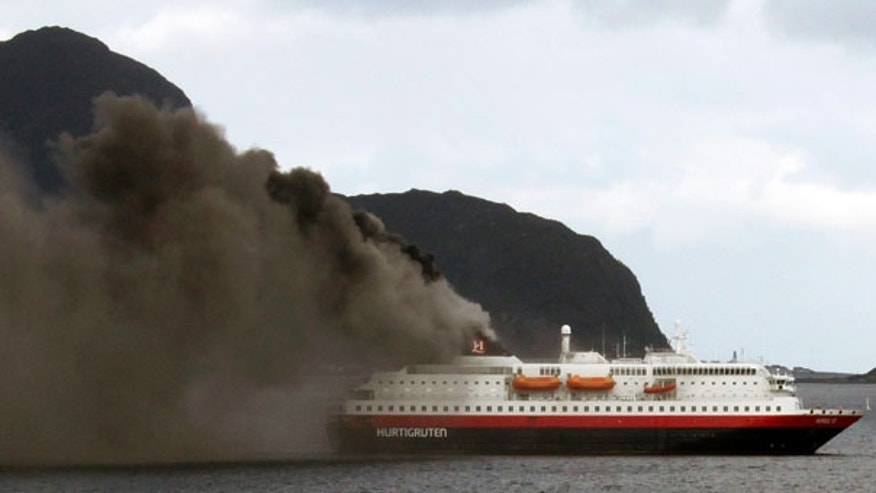 Sept. 15: Norwegian cruise ship, MS Nordlys, one of the Hurtigruten ships billows smoke as it approaches Alesund in western Norway.