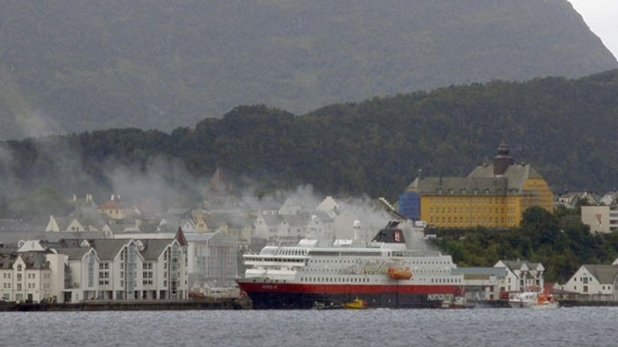 Sept. 15: Smoke rises from the Norwegian cruise ship, MS Nordlys, one of the classic Hurtigruten ships alongside Alesund in western Norway.