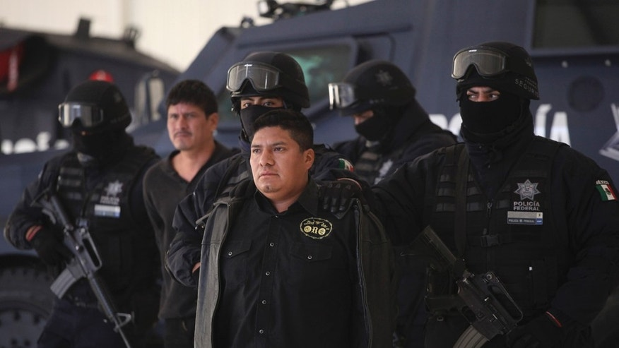 "Federal Police agents escort Flavio Mendez Santiago, center, alias ""El Amarillo,"" alleged member and co-founder of the Zetas drug cartel, during a presentation to the media in Mexico City, Tuesday, Jan. 18, 2011. Mendez Santiago was detained in Villa de Etla, Mexican state of Oaxaca, some 400 km southeast of Mexico City, on Monday. (AP Photo/Alexandre Meneghini)"