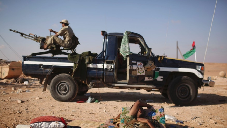 A former rebel fighter rests at the northern gate of Bani Walid, Libya, Saturday, Sept. 17, 2011. Revolutionary fighters struggled to regroup Saturday outside the loyalist stronghold of Bani Walid after being driven back by fierce resistance from followers of Muammar Qaddafi, temporarily quieting one battlefield.
